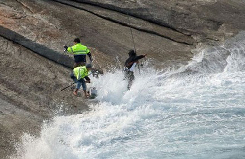 Fishers get swamped by wave on rocks